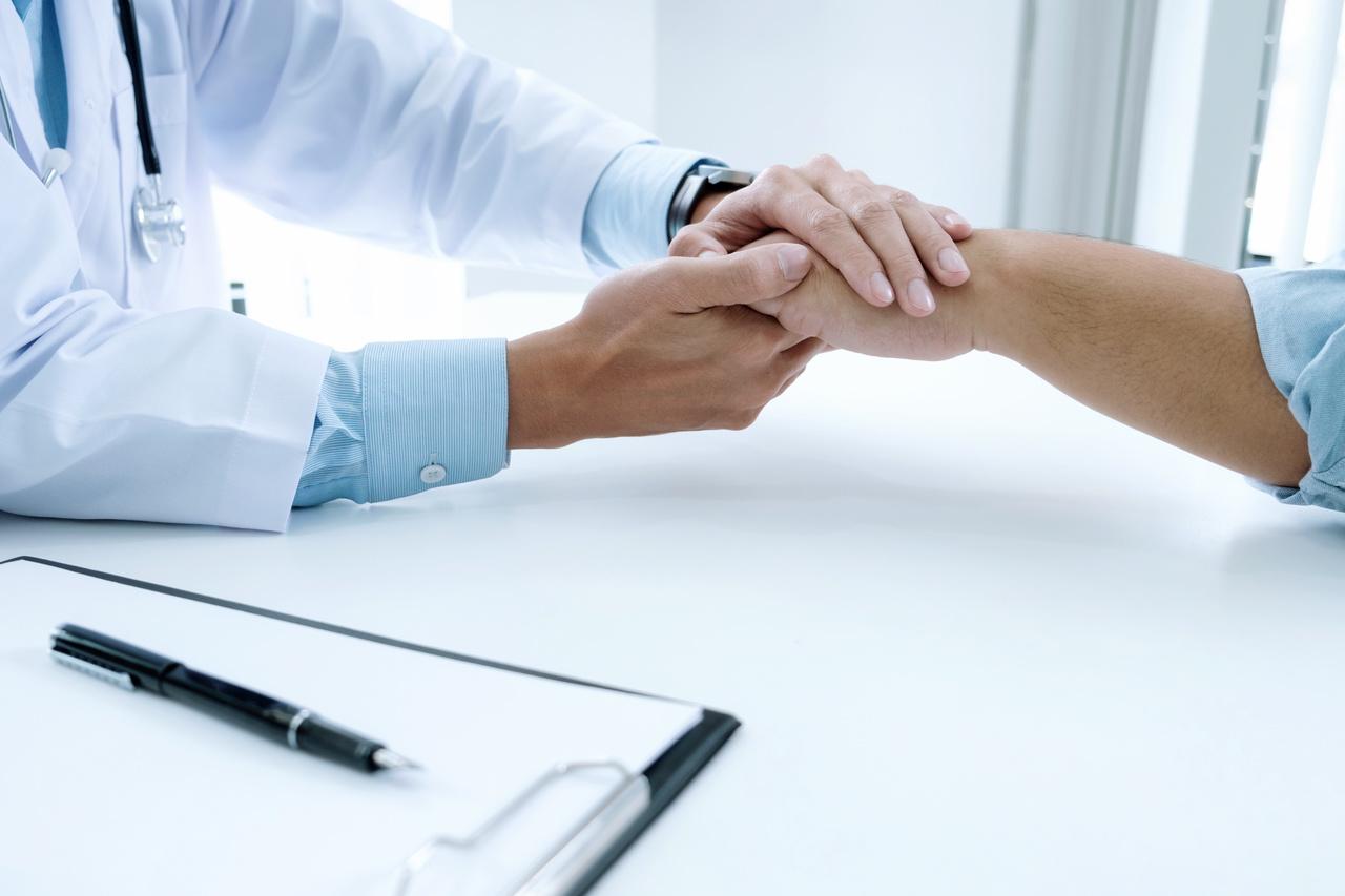 Na foto, um médico aparece cumprimentando um paciente e/ou amigo