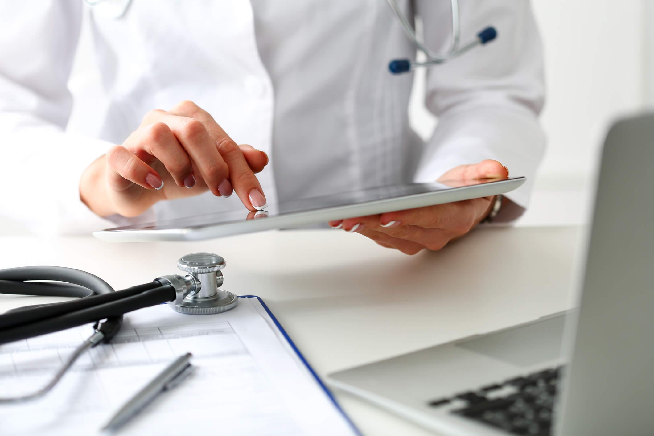 Médica fazendo a gestão de pacientes através de um tablet