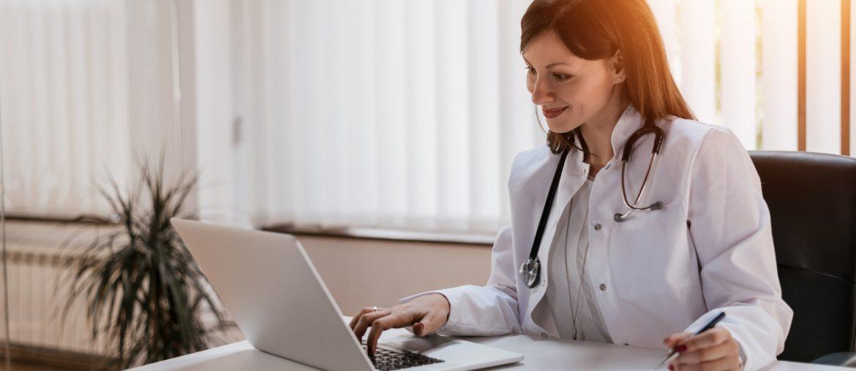 Médica olhando no computador um site para clínicas